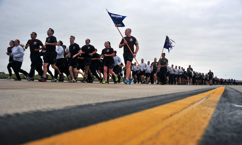 Members of Team Whiteman complete the final stretch of the Wingman Day flightline run at Whiteman Air Force Base, Mo., Oct. 9, 2015. Events were held throughout the day to strengthen and sustain a resilient Air Force community that values mental, physical, social, and spiritual fitness. (U.S. Air Force photo by Airman 1st Class Jovan Banks/Released)