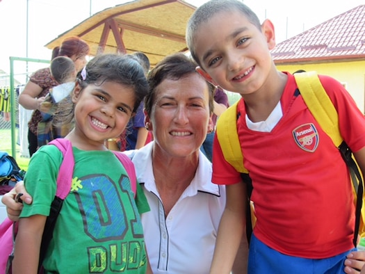 Senior Master Sgt. Pam Pittman, assigned to the 123rd Expeditionary Fighter Squadron,  pauses for a photography with children at a local orphanage near Campia Turzii, Romania, Sept. 19, 2015. (Photo courtesy of 123rd Expeditionary Fighter Squadron)