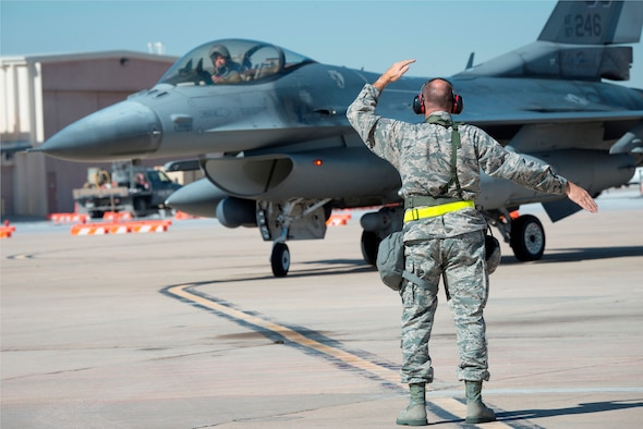 U.S. Air Force Tech. Sgt. Robbin Bruning, 140th Maintenance Squadron, Colorado Air National Guard, ushers in an F-16 Fighting Falcon during the wing's readiness inspection at Buckley Air Force Base, Aurora, Colo., Oct. 16, 2015. This training is a part of the 140th Wing's four-day Wing Wartime Readiness Inspection, the U.S. Air Force's new evaluation system for wartime, contingency and force sustainment readiness. (U.S. Air National Guard photo by Tech. Sgt. Wolfram M. Stumpf)