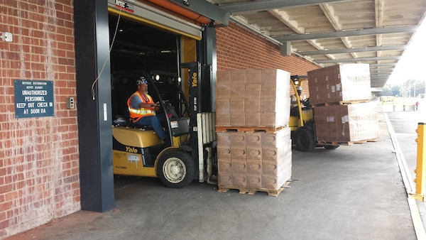 A DLA Distribution Albany employee moves a pallet of MRE's to be shipped to Fort Jackson, S.C., to aid in the Hurricane Joaquin disaster relief.