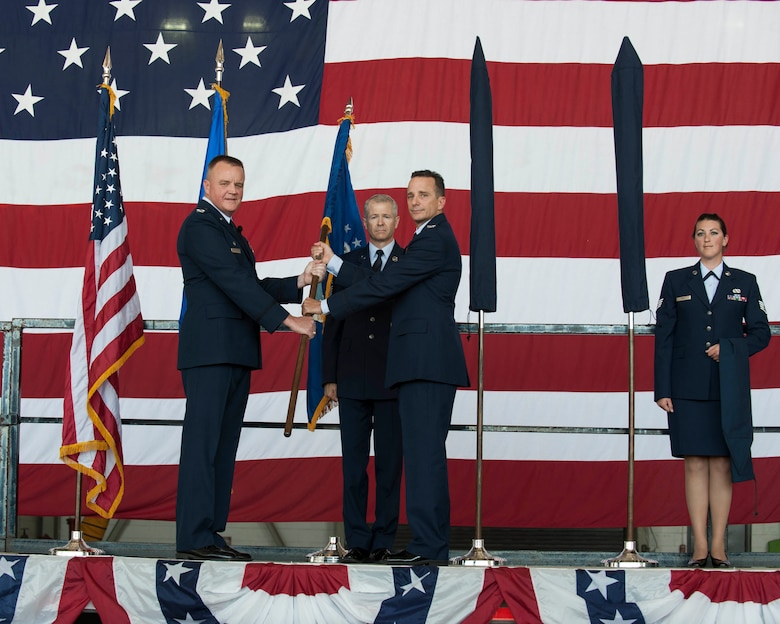 Air Force Col. Bruce Cox, 307th Bomb Wing commander, left, passes a guidon to Col. Denis Heinz, 489th Bomb Group commander, during the 489th BG Reactivation ceremony Oct. 17, 2015, at Dyess Air Force Base, Texas. The unit will be furthering Total Force Integration, which aims to integrate active duty Air Force, Air Force Reserve and Air National Guard components, by using the B-1B Lancers at Dyess for their mission and the 7th Bomb Wing's mission . (U.S. Air Force photo by Airman Quay Drawdy)