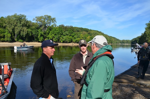 Dan Kelner, left, district mussel biologist, and Nathan Eckert, U.S. Fish and Wildlife Service mussel biologist, talk with Secretary of the U.S. Department of the Interior Ken Salazar during an endangered mussel release in the Mississippi River Aug. 17, 2012.