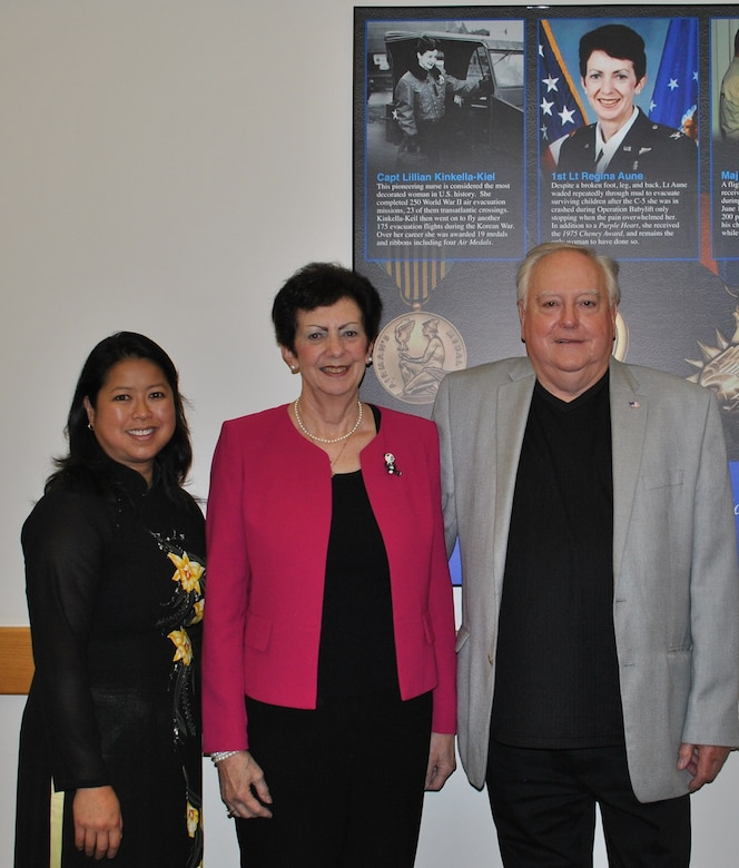 """Aryn Lockhart (from left), retired Lt. Col. Regina C. Aune and retired Chief Master Sgt. Ray Snedegar stand in front of a piece of art honoring """"Those Who Save,"""" which includes a tribute to then 1st Lt. Regina Aune. The artwork is in Building 1 at Joint Base San Antonio-Lackland, Texas. (U.S. Air Force photo/Carole Chiles Fuller/Released)"""