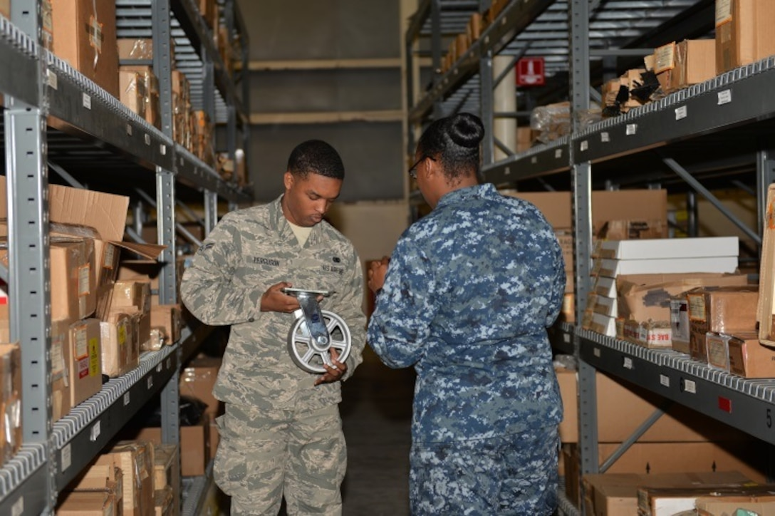 Airman 1st Class Kristoffer Ferguson, 96th Logistics Readiness Squadron F-35 supply apprentice, and Petty Officer 2nd Class Whitney Moss, 33rd Maintenance Squadron logistics specialist, verify equipment barcodes at Eglin Air Force Base, Fla., Oct. 15, 2015. The 96th LRS supplies the F-35 Lightning II A and C parts and equipment to the 33rd Fighter Wing and Navy Strike Fighter Squadron 101 Grim Reapers. (U.S. Air Force Photo/Senior Airman Andrea Posey)