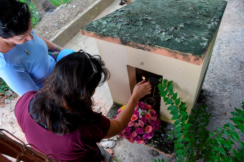 Operation Babylift survivor Aryn Lockhart, lights a memorial candle at a shrine commemorating those lost during the crash of a C-5A in Saigon, Vietnam, in April 1975. More than 70 orphans bound for the United States died in the crash.