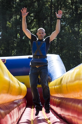 A Marine jumps on a bouncy house during the Headquarters and Headquarters Squadron fall festival at the chapel aboard Marine Corps Air Station Beaufort Oct. 17. Marines, spouses and children were invited for a day of autumn activities to kick off the holiday season. The Marine is with H&HS.