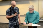 Matthew Leistikow, a journalism instructor in the Basic Mass Communication Specialist Course at the Defense Information School on Fort Meade, Md., gives Navy Seaman Apprentice William Andrews, an Atlanta native, after-school training Sept. 22, 2015. Formerly a petty officer first class, Leistikow chose to separate from the Navy to remain a DINFOS instructor instead of continuing his military career, possibly as a chief petty officer.