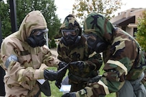 Airmen of the 911th Operations Group examine M8 paper outside of the operations building at the Pittsburgh International Airport Air Reserve Station, Oct. 4, 2015. Airmen dressed in mission oriented protective posture gear during a chemical, biological, radiological, nuclear and explosives exercise that took place here during the unit training assembly. (U.S. Air Force photo by Senior Airman Marjorie A. Bowlden)