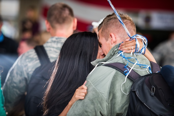 """Cara Carnafel (left) embraces her husband, Airman 1st Class Alex Carnafel, 726th Air Control Squadron air surveillance member, for the first time in six months Oct. 18, 2015 at Mountain Home Air Force Base, Idaho. Moments before, Cara said """"It's been so long but it's all going to be worth it in the next 10 minutes; I just can't wait to see him."""" Alex was deployed to Southwest Asia with the 726th ACS. (U.S. Air Force photo by Airman 1st Class Connor J. Marth)"""