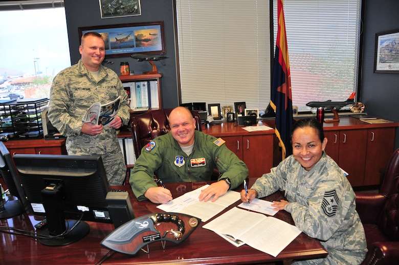 Col. Gary Brewer, Jr., 161st Air Refueling Wing commander (center), and Chief Master Sgt. Martha Garcia, wing command chief, pledge donations to the 2015 Combined Federal Campaign, Oct. 20, while 2nd Lt. David Hutchinson, the wing's CFC Representative,  explains the donation process. The campaign is open through Dec. 15. (U.S. Air National Guard photo by Master Sgt. Kelly Deitloff)