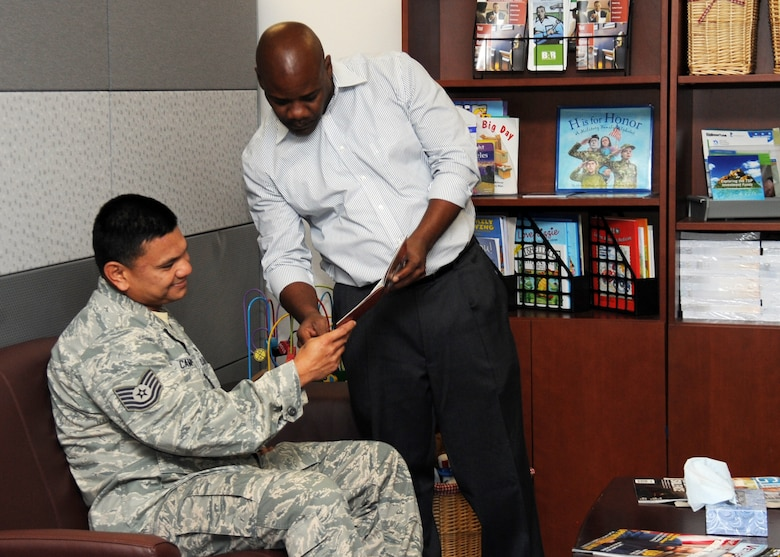 John Howard, a student intern from the University of Southern California's Adults and Healthy Aging Department assists Tech. Sgt. Johnny Campos from the Space and Missile Systems Center's Chaplain's office with family-based educational literature available at the Airman and Family Readiness Center's Discovery Center at Los Angeles Air Force Base in El Segundo, Calif. A partnership between USC's Masters in Social Work program and SMC will play a critical role in preparing future graduates for contemporary clinical issues in their chosen profession by providing.an understanding of military culture and the commitment that is made by the men and women of the armed forces, as well as the sacrifices of their families. (U. S. Air Force photo/Van De Ha)