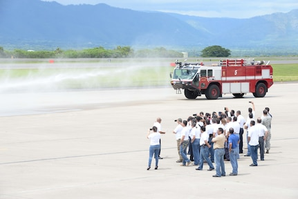 Members from the Honduran Defense College watch as the 612th Air Base Fire Department responds to a controlled fire during a visit to Soto Cano Air Base, Honduras, Oct. 16, 2015. The visit provided a better understanding of JTF-Bravo's mission and capabilities for the Defense College members. (U.S. Air Force photo by Senior Airman Westin Warburton/Released)