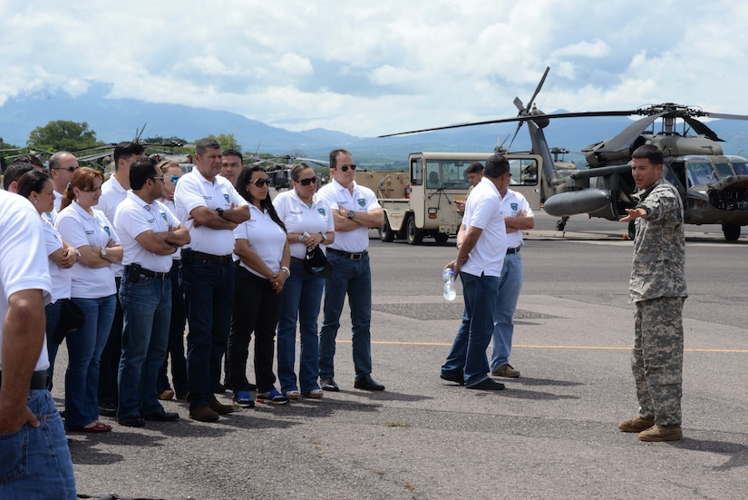 U.S. Army Sgt. Ruben Ramos, 1-228 aviation regiment, explains how the MH-60 Black Hawk helicopter works for the Honduran Defense College during a visit to Soto Cano Air Base, Honduras, Oct. 16, 2015. The visit provided a better understanding of JTF-Bravo's mission and capabilities for the Defense College members. (U.S. Air Force photo by Senior Airman Westin Warburton/Released)