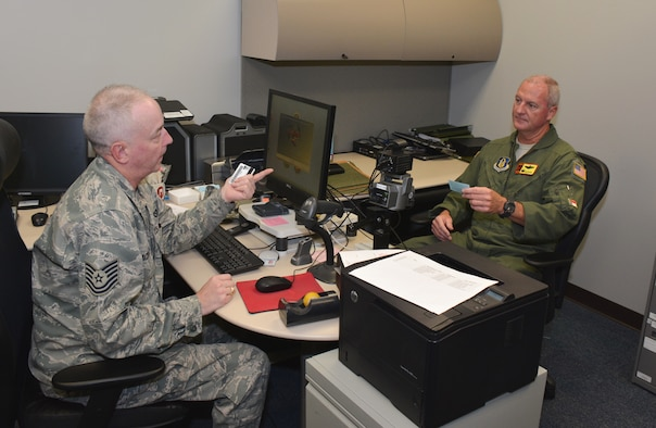 "Tech. Sgt. James ""Butch"" Blackwell (left), 507th Force Support Squadron, issues the first common access card to 507th Air Refueling Wing commander, Col. Brian ""B.S."" Davis at the new Military Personnel Section location in Building 1048, Room 112, Oct. 20, 2015 at Tinker Air Force Base, Okla. (U.S. Air Force photo/Maj. Jon Quinlan)"