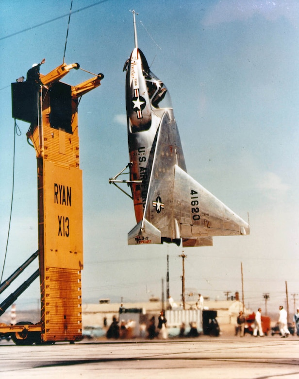 "The museum's X-13 making a test flight in 1957. The X-13 ""landed"" by hooking onto a cable at the top of the raised platform. This trailer-mounted platform could then be lowered to a horizontal position. (U.S. Air Force photo)"