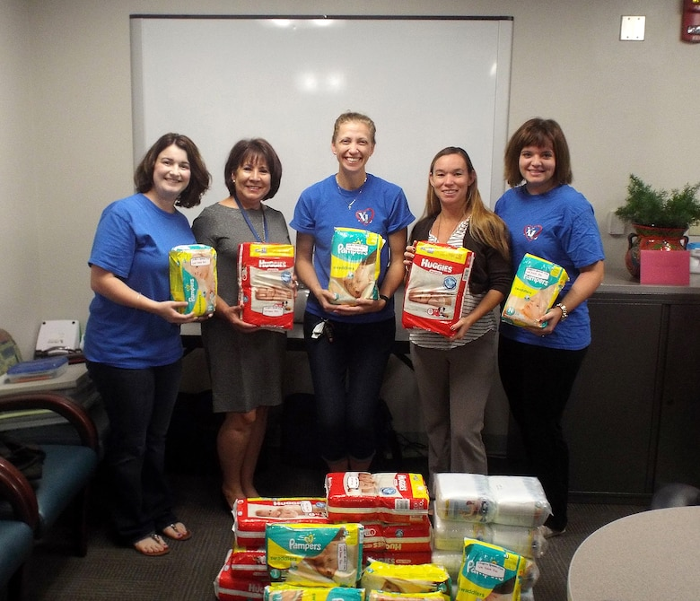 From left, Priscilla Turner, Laughlin Spouses' Club president, Silvia Gonzalez, Family Advocacy Program assistant, Rachel Emmerthal, club vice-president, Casey Mollen, Family Advocacy Program Outreach manager, and Hillary Bailey, club charitable chair, pose with donated diapers at the Family Advocacy office on Laughlin Air Force Base, Texas, Oct. 5, 2015. In partnership with the 47th Medical Group's Family Advocacy Program, the Laughlin Spouses' Club contributed over 900 diapers to enhance the 'Bundles for Babies' program offered to new moms affiliated with the base. (Photo provided by the Laughlin Spouses' Club)(Released)