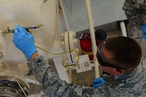 Staff Sgt. Jermey Manning, 2nd Logistics Readiness Squadron fuels laboratory technician, siphons jet fuel from a pump at Barksdale Air Force base, La., Oct. 14, 2015. The B-52 Stratofortress can carry 47,975 gallons of fuel and the pump house is capable of providing the fuel quickly. (Air Force Photo/Airman 1st Class Luke Hill)