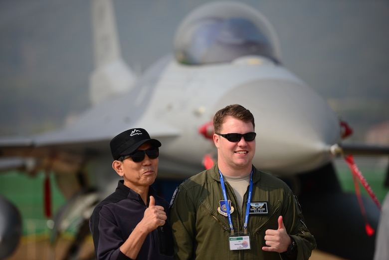 Capt. Nathan Walker, 35th Fighter Squadron, poses with a local Korean in front of an F-16 Fighting Falcon from Kunsan Air Base, at the Seoul International Aerospace and Defense Exhibition held just outside of Seoul, Republic of Korea, Oct. 19, 2015. The Seoul ADEX gives American service members a chance to showcase their outstanding aircraft and equipment to the Korean public. (U.S. Air Force photo/Staff Sgt. Amber Grimm)