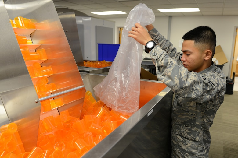 Airman 1st Class Michael Pacla, 56th Medical Support Squadron pharmacy technician, refills the prescription bottle dispenser at Luke Air Force Base, Arizona, Oct. 19, 2015. The bottles get loaded through the conveyor belt and get labelled at user request autonomously. (U.S. Air Force photo by Senior Airman James Hensley)