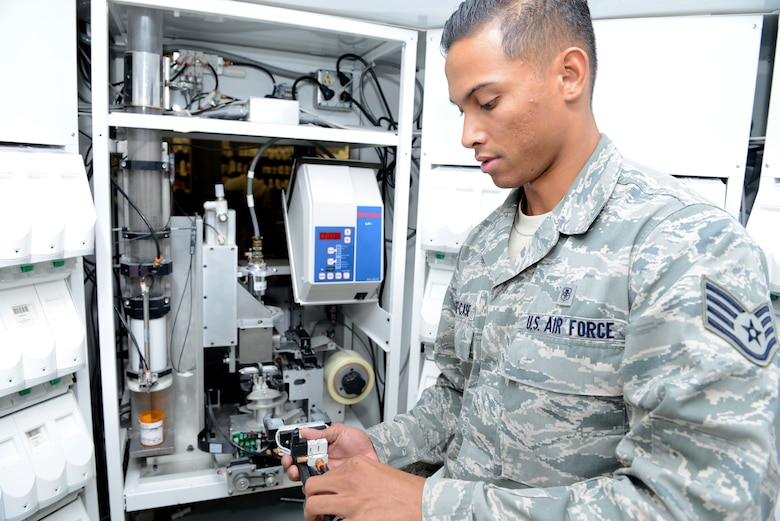 Staff Sgt. Aaron Munoz-Case, 56th Medical Support Squadron Arizona Refilling Center acting NCO in charge, adjusts the robotic arm at Luke Air Force Base, Arizona, Oct. 19, 2015. The robotic arm system helps Airmen at the ARC refill approximately 60 percent of all prescriptions. (U.S. Air Force photo by Senior Airman James Hensley)