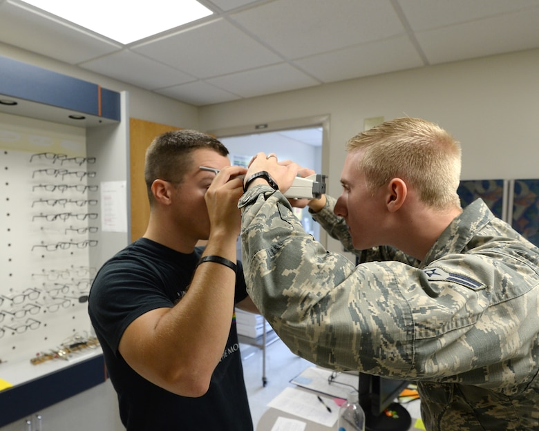 Airman 1st Class Jordan Cutaia, 325th Aerospace Medicine Squadron optometry technician, uses a device to gauge a patient's eyesight Sept. 30.  Optometry technicians like Cutaia are responsible for processing eyewear prescriptions for military spectacles; they also perform and manage optometry clinic activities. 325th AMDS provide medical, dental, and preventive care, enabling all wing and associate units to maximize readiness and combat capability. (U.S. Air Force photo by Airman 1st Class Cody R. Miller/Released)