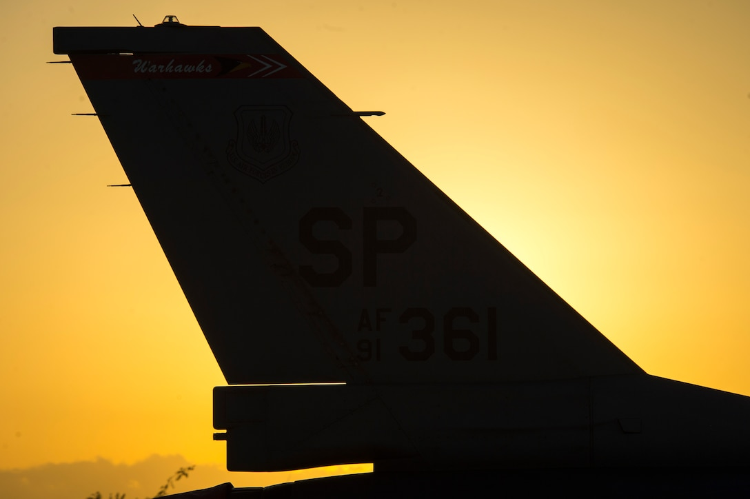 TRAPANI AIR BASE, Italy - The tail of an F-16 Fighting Falcon fighter aircraft assigned to the 480th Fighter Squadron at Spangdahlem Air Base, Germany, sits in front of the sun before the start of the Trapani Air Show at Trapani Air Base, Italy, Oct. 19, 2015. Two F-16s from Spangdahlem participated in the air show, one for a formation flyover and the other for a static display. The Trapani Air Show kicked off Trident Juncture 2015, a training exercise involving more than 30 Allied and Partner Nations taking place throughout Italy, Portugal and Spain. (U.S. Air Force photo by Airman 1st Class Luke Kitterman/Released)