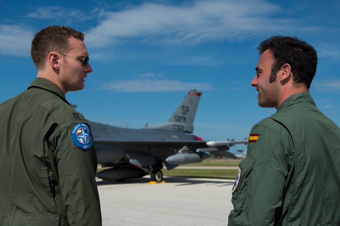 An F-16 Fighting Falcon fighter aircraft pilot, assigned to 480th Fighter Squadron, Spangdahlem Air Base, Germany, talks with a Spanish Air Force pilot during the Trapani Air Show at Trapani Air Base, Italy, Oct. 19, 2015. The Trapani Air Show kicked off Trident Juncture 2015, a training exercise involving more than 30 Allied and Partner Nations taking place throughout Europe mainly in Italy, Portugal and Spain. (U.S. Air Force photo by Airman 1st Class Luke Kitterman/Released)