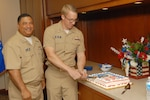 Navy Capt. Ricardo Wilson, DLA Troop Support director of Process Procurement Support (left), and Navy Lt. Andrew Heisler (right), of the Subsistence supply chain, cut a ceremonial birthday cake during a celebration Oct. 13 in Philadelphia honoring the service's 240th birthday.