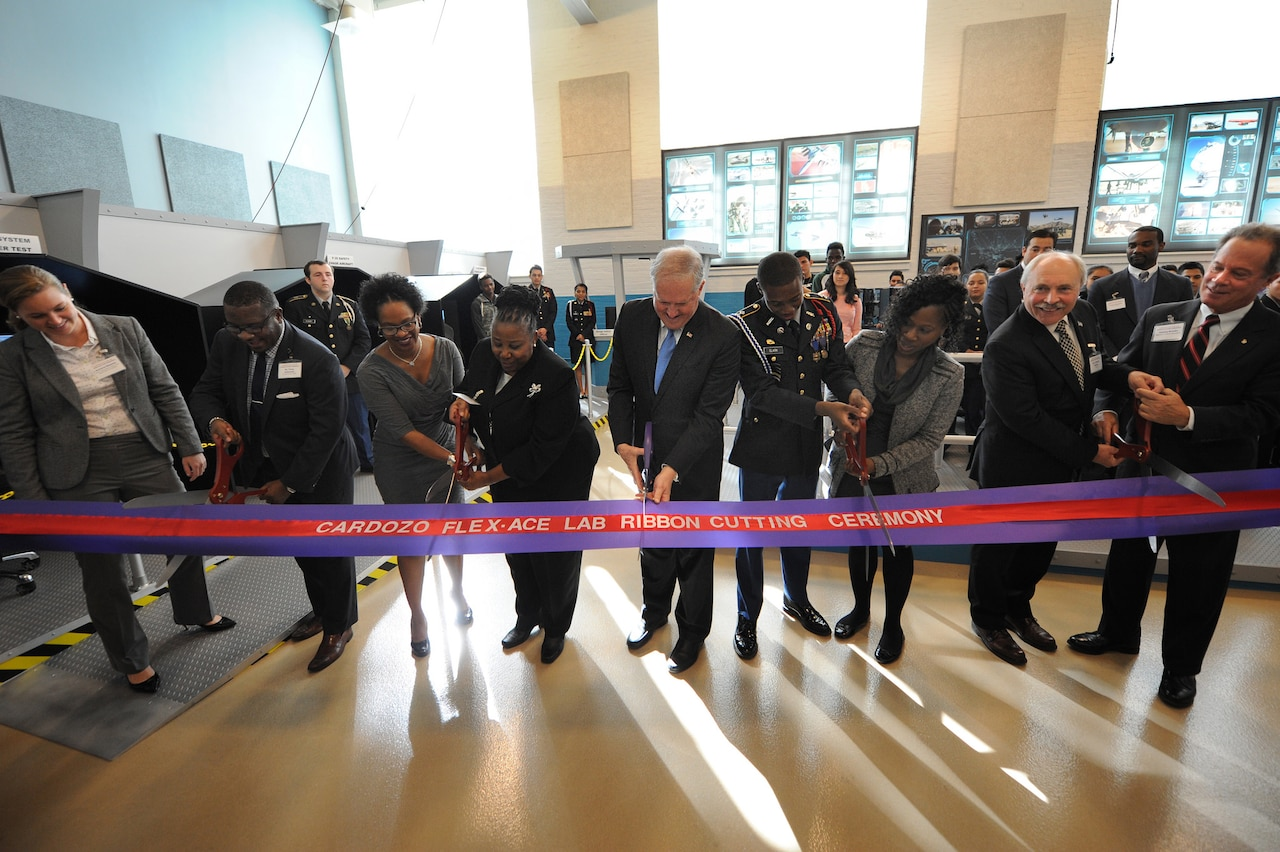 Frank Kendall, center, undersecretary of defense for acquisition, technology and logistics, helps to cut the ceremonial ribbon symbolizing the opening of a FLEX-ACE Lab at Francis L. Cardozo Education Campus, Washington, D.C., Oct. 20, 2015. The Flexible Aviation Classroom Experience, or FLEX-ACE, replicates a test-range control room and operations center with state-of-the-art computers, flight simulators and a miniature air-traffic-control tower. The FLEX-ACE Lab is established through a partnership with Cardozo, the Office of the Assistant Secretary of Defense for Research and Engineering, and the DoD Test Resource Management Center. DoD photo by Marvin Lynchard