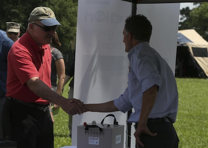 Retired Vice Adm. Dennis McGinn (left), the Assistant Secretary of the Navy for Energy, Installations and Environment, speaks to a representative of one of the civilian companies responsible for developing new, more energy efficient batteries for the Marine Corps at the Expeditionary Energy Concepts demonstration aboard Camp Lejeune, N.C., June 24, 2015. The demonstration drew VIPs from Marine Corps, Department of Defense and civilian organizations, as well as members of other military services and other countries.
