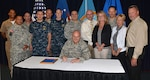 Defense Logistics Agency Aviation team members pose with DLA Aviation Commander Air Force Brig. Gen. Allan Day Sept. 17, 2015 in the commander's conference room on Defense Supply Center Richmond, Virginia, as he signs volume one of the agency's retail supply manual. The manual, began 22 months ago, outlines day-to-day operational procedures designed to provide supply excellence for Air Force retail operations.