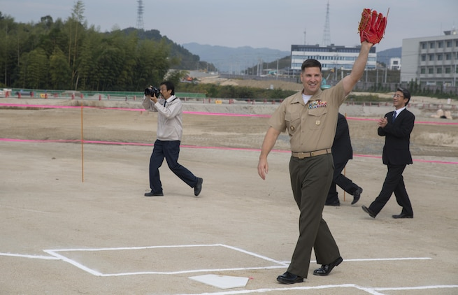 Col. Robert V. Boucher, commanding officer of Marine Corps Air Station Iwakuni, Japan, waves after the first pitch at the ground breaking ceremony at Atagoyama Baseball Field in Iwakuni City, Oct. 15, 2015. A first pitch on the future baseball field demonstrated the special bond between Iwakuni City and the air station.