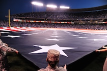 Members of Team Whiteman take part in a flag ceremony during the pregame ceremonies of the American League Championship Series at Kauffman Stadium in Kansas City, Mo., Oct. 16, 2015. More than 100 service members participated in the flag ceremony which was accompanied by a B-2 Spirit flyover. (U.S. Air Force photo by Senior Airman Joel Pfiester/Released)