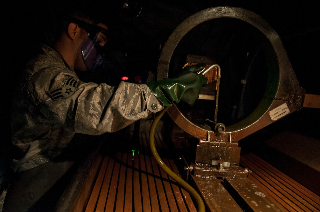 Senior Airman Michael Vigil, 19th Maintenance Squadron Non-Destructive Inspection journeyman, runs an aircraft part under a chemical bath Oct. 14, 2015, on Little Rock Air Force Base, Ark. NDI Airmen find tiny faults in aircraft parts by running them through multiple chemical baths. (U.S. Air Force photo by Airman 1st Class Mercedes Muro)