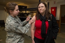 Patty McCormick, wife of U.S. Air Force Master Sgt. Michael McCormick, 726th Air Mobility Squadron quality assurance superintendent, is administered her flu shot by U.S. Air Force Capt. Amy Lynn, 52nd Medical Operations Squadron women's health clinic element leader, during a disease containment plan exercise Oct. 21, 2015, at Spangdahlem Air Base, Germany. Common side effects for the injected vaccine include soreness, redness or swelling where the shot was received, fever, aches or cough. (U.S. Air Force photo by Staff Sgt. Christopher Ruano/Released)