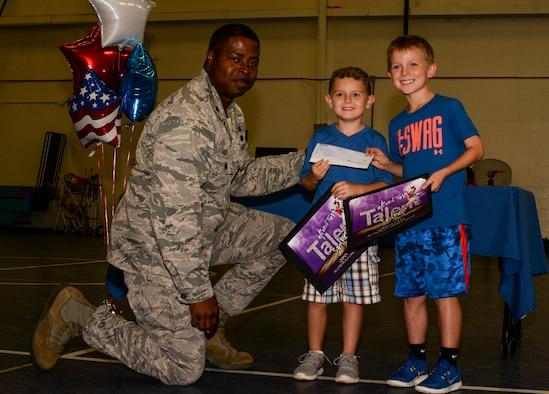 U.S. Air Force Lt. Col. Nathan Palmer, 23d Mission Support Group deputy commander, poses with Quinn Burgess, son of Tech. Sgt. Daniel Burgess, 41st Helicopter Maintenance Unit assistant section chief, and Garrett Locke, son of Col. Joseph Locke, 93d Air Ground Operations Wing commander, after presenting them with award certificates and a check for $200, September 9, 2015, at Moody Air Force Base Ga. Quinn, Garrett, and Devinn Dunn son of retired Master Sgt. James Dunn, danced their way to first place in the Moody Talent Search and second place in the Air Force wide Operation Talent Search. (U.S. Air Force photo by Airman 1st Class Janiqua P. Robinson/Released)
