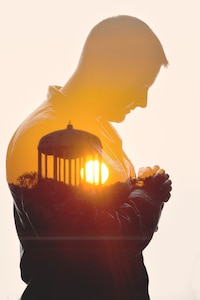 Master Sgt. Jermey Lawley, 11th Wing Equal Opportunity superintendent, and the sunset over Joint Base Andrews, Md., in a double exposure photograph to represent the spiritual fitness pillar of Comprehensive Airmen Fitness. (U.S. Air Force graphic by Airman 1st Class Philip Bryant/Released)