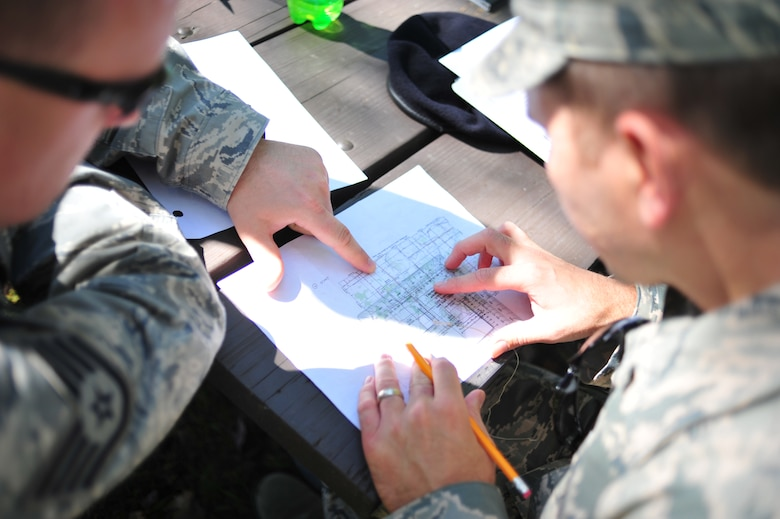 Security Forces Airmen of the 180th Fighter Wing prepare to start a land navigation course by examining a map grid at Oak Openings Metro Park in Swanton, Ohio on Sep. 27, 2015. The 180th Security Forces Squadron used old-school navigations tools, such as a compass and map, to maneuver a training course that prepares Airmen for scenarios when advanced technology may fail and leave them to rely only on the most basic resources. (Ohio Air National Guard photo by Staff Sgt. John Wilkes)