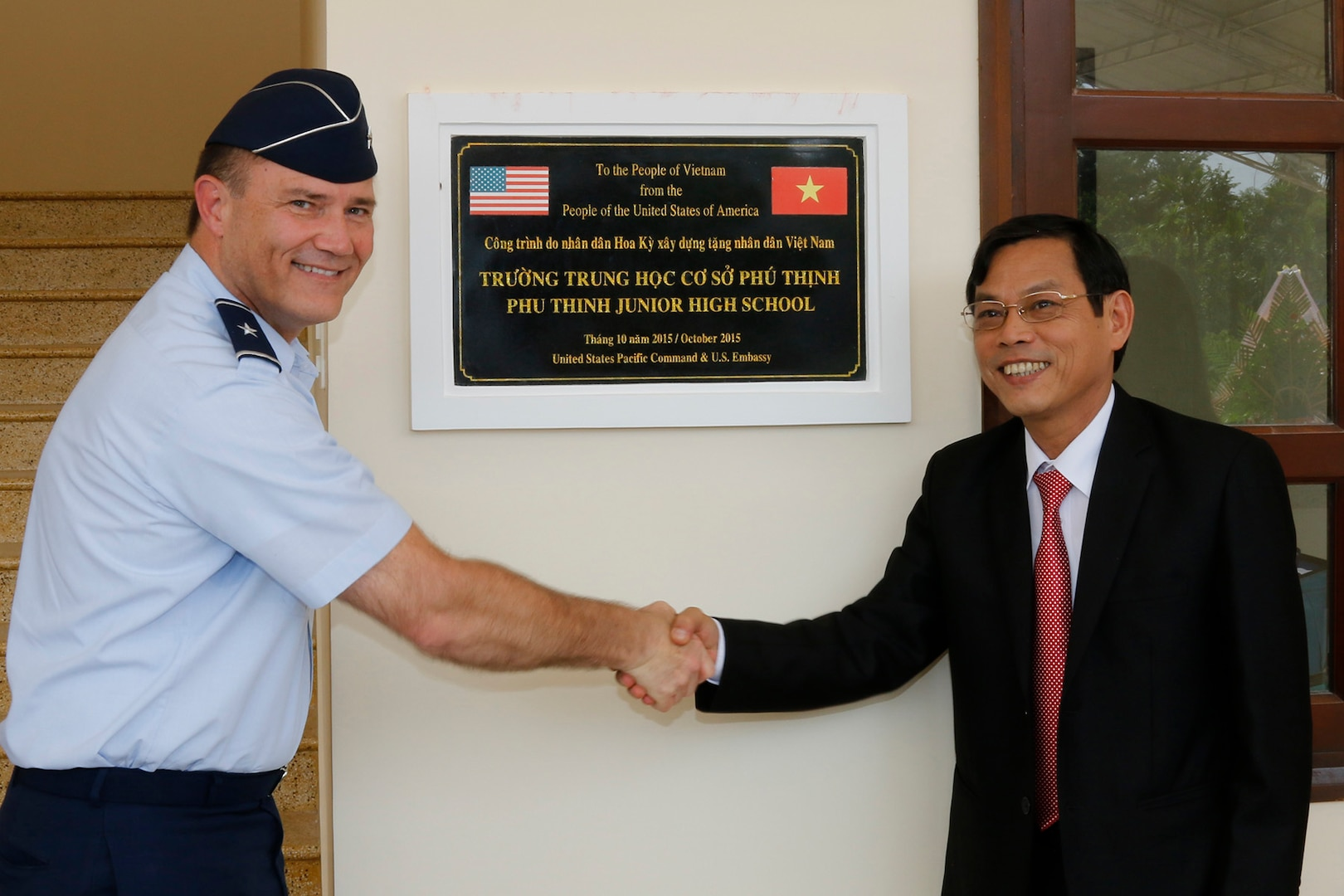 Brig. Gen. Michael E. Stencel, adjutant general, Oregon, and Nguyen Chin, Deputy Chairman of the Quang Nam Provincial People's Committee, unveil a plaque memorializing U.S. and Vietnamese cooperation in building a new intermediate school in Phu Tinh Village in the Quang Nam Province of Vietnam, Oct. 21, 2015. The new school was built in cooperation between the U.S. and Vietnam and has a secondary use as a shelter during natural disasters.