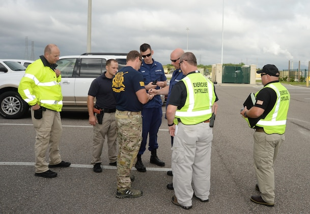 Bomb squad technician and law enforcement officer look on as a U.S. Coast Guard team outlines a floor lay-out and identifies a safe entry point into a building after the team's K-9 Unit alerts the detection of a bomb at the location. The drill was conducted during a full-scale exercise at Marine Corps Support Facility Blount Island, Jacksonville, Fla., recently. Exercise controllers/evaluators monitor the mutual aid partners' verbal exchange, responses and plan of action for handling the potential threat.