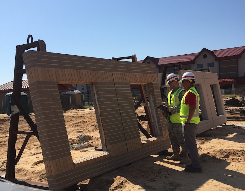 1st Lt. Thomas Zarack (left) of the Technical Engineer Competency Development Program and Romeo Enriquez (right), a Mechanical Engineer in the Construction Division, perform a quality assurance inspection on a concrete panel soon to be placed on the 600-room Advanced Individual Training Phase II Barracks at Fort Gordon Oct. 16.