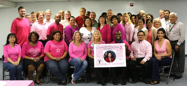 Defense Logistics Agency Energy Aerospace Energy employees pose for a photograph during a breast cancer awareness event held in San Antonio, Oct. 22. Two breast cancer survivors spoke at the event, and a poster was made in memory of an employee, Sylvia Gonzales, who lost her battle to breast cancer in 2010.