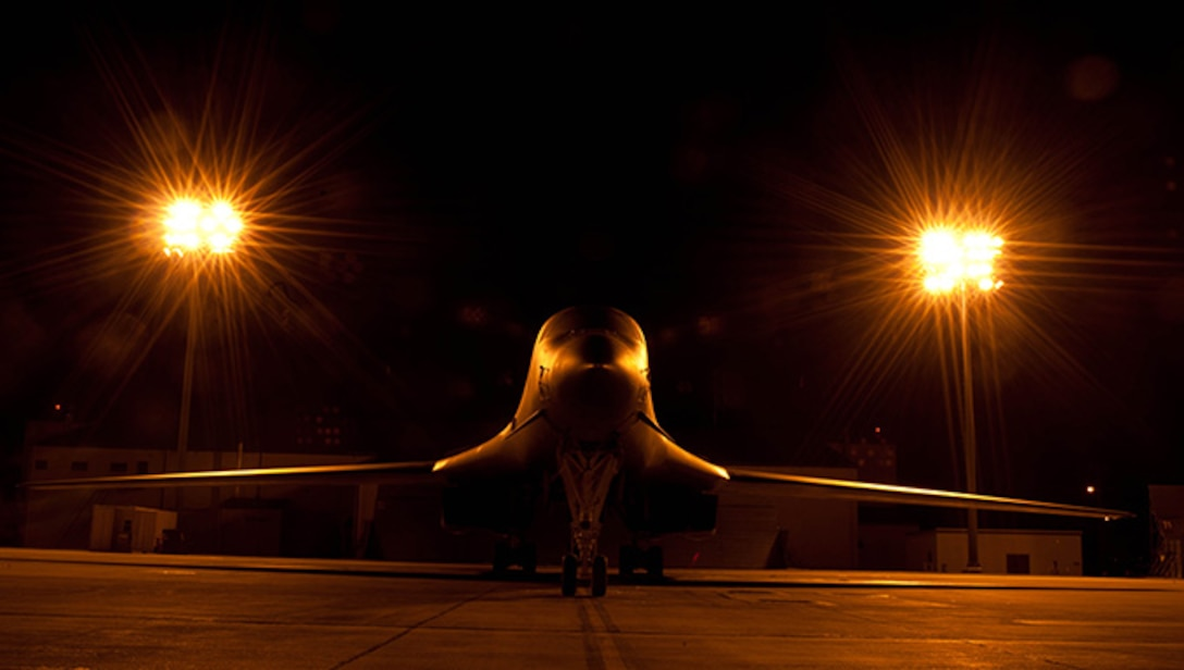 A B-1 bomber shrouded in the glow of lights in the aircraft parking area sits silently at Ellsworth Air Force Base, S.D., July 24, 2012. The B-1 is a long-range, multi-role heavy bomber that can reach speeds of 900-plus miles per hour. (U.S. Air Force photo by Airman 1st Class Zachary Hada/Released)