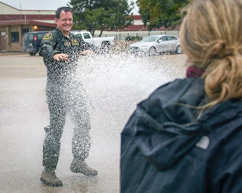 """Lt Col. Darren """"Shead"""" McTee gets the traditional fini-flight hose-down from his family following his final flight with the 5th Flying Training Squadron at Vance Air Force Base, Okla. (Courtesy photo)"""
