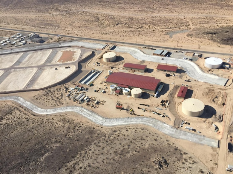 Aerial view of Fort Irwin's new water treatment Plant (Courtesy photo provided Sgt. Maj. (RET) Scott Blum) The plant (red roofs and four water tanks) is the main purification system of the water treatment plant. The concrete channels around the plant are built to safeguard the plant from storm water events and also provides full containment of the plants processing water in case of catastrophic failure of the plant. The ponds shown on the top of the photo are the evaporation ponds to handle less than 1% of the brine water remnants from the water treatment system.  The project is the design-build of a six million gallon per day water treatment plant. The new plant will use a three-stage, electro-dialysis reversal (EDR) water treatment plant that treats all contaminants found in Fort Irwin's ground water in accordance with federal and state requirements. The plant will include: an electro-dialysis reversal (EDR) primary treatment, lime softening clarifiers, lime solids thickeners, lime sludge lagoons, reverse osmosis (RO) filters, brine treatment facility, concentrate equalization basins and a mechanical evaporator tower and feed tank, and three evaporation ponds to achieve the post's 99 percent water recovery rate. The project also includes water system improvement and supporting utilities and infrastructure upgrades