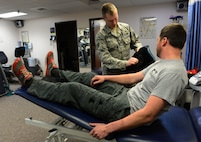 U.S. Air Force Staff Sgt. Michael White, a 354th Medical Group physical therapy technician, helps Staff Sgt. Barret Chappelle, a 354th Security Forces Squadron military working dog handler, put on the compression pack Oct. 22, 2015, at Eielson Air Force Base, Alaska. This helps alleviate pain after Chappelle's physical therapy session by mixing compression with cold on the affected area. (U.S. Air Force photo by Airman 1st Class Cassandra Whitman/Released)