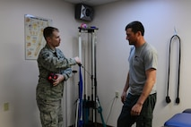 U.S. Air Force Staff Sgt. Michael White, a 354th Medical Group physical therapy technician, demonstrates an exercise to Staff Sgt. Barret Chappelle, a 354th Security Forces Squadron military working dog handler, Oct. 22, 2015, at Eielson Air Force Base, Alaska. White demonstrates all exercises to his patients before they do them on their own. (U.S. Air Force photo by Airman 1st Class Cassandra Whitman/Released)