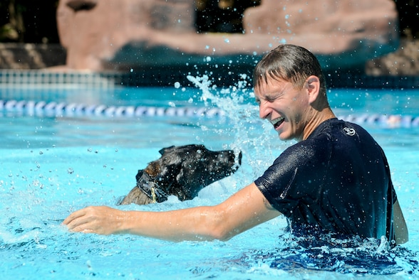 Staff Sgt. Jenings Casey, 6th Security Forces Squadron military working dog handler, and MWD Branco splash in a wave pool after a water aggression training exercise at a local water park in Tampa, Fla., Oct. 15, 2015. The water aggression training offers a unique opportunity for working dogs to become familiar with water. (U.S. Air Force photo by Airman 1st Class Mariette M. Adams/Released)
