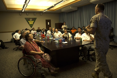 Members of the Okinawa Prefecture Defense Association listen to Col. Peter Lee's response during the question and answer portion of an educational tour Oct. 22 on Marine Corps Air Station Futenma, Okinawa, Japan. Lee explained to guests the mission of tenant units on MCAS Futenma and highlighted the Marines' contribution to the Okinawa community as well as disaster relief efforts and operational capabilities of the air station throughout the Asia-Pacific region. Lee is the commanding officer of MCAS Futenma, Marine Corps Installations Pacific and a New Rochelle, N.Y., native.