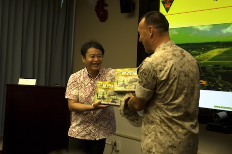 Asao Ogimi, left, presents gifts to Col. Peter Lee during an educational tour Oct. 22 on Marine Corps Air Station Futenma, Okinawa, Japan. During the tour, members of the Okinawa Prefecture Defense Association learned about the history and tenant commands of MCAS Futenma and their capabilities. After a question and answer session, the members boarded a bus for a windshield tour of the installation. Ogimi is a chairman with the Okinawa Prefecture Defense Association. Lee is the commanding officer of MCAS Futenma, Marine Corps Installations Pacific and a New Rochelle, N.Y., native.